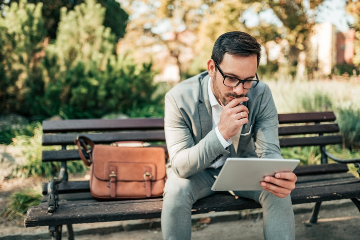 Young businessman working on tablet outdoors.