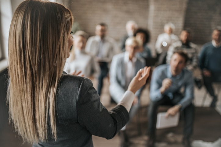 Female manager talking to large group of her colleagues on a business seminar.
